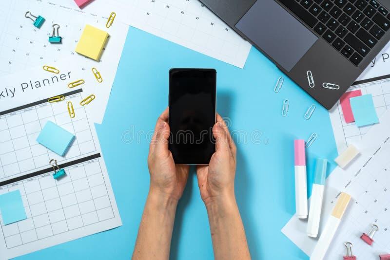 Smartphone van de vrouwenholding dichtbij ontwerper op blauwe pastelkleurachtergrond met laptop en kantoorbehoeften royalty-vrije stock afbeelding