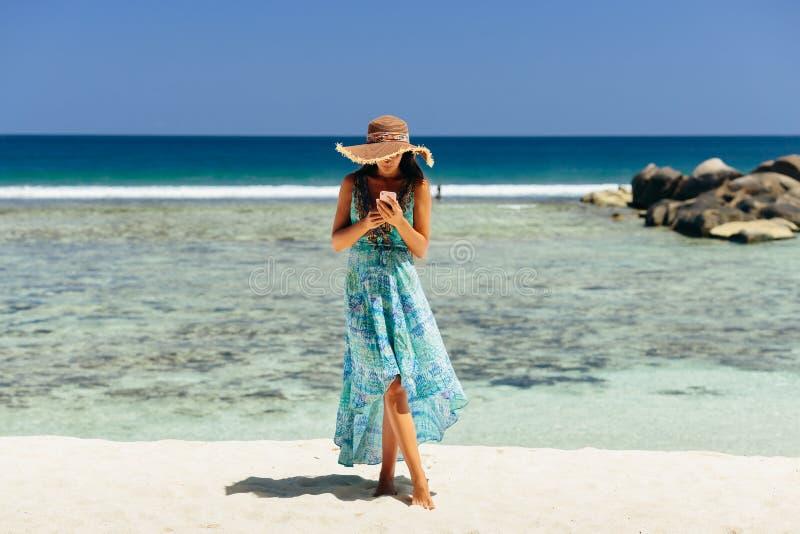 Smartphone van de vrouwenholding op strand stock foto