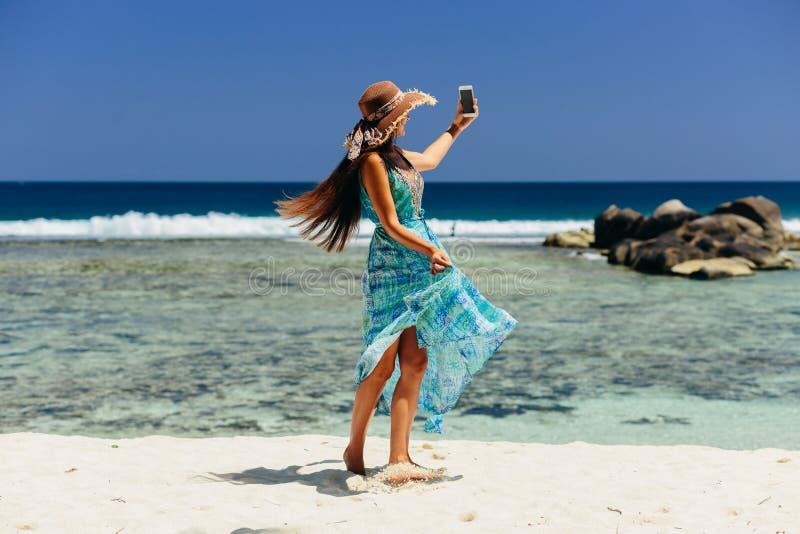 Smartphone van de vrouwenholding op strand stock afbeeldingen