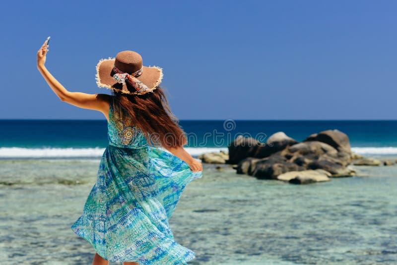 Smartphone van de vrouwenholding op strand stock foto's