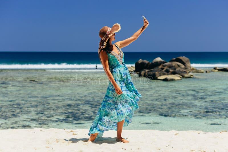 Smartphone van de vrouwenholding op strand royalty-vrije stock fotografie