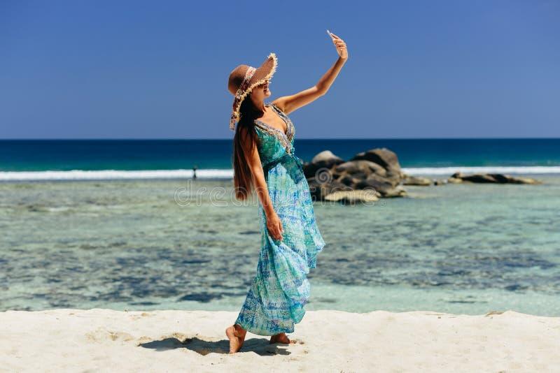 Smartphone van de vrouwenholding op strand royalty-vrije stock afbeeldingen