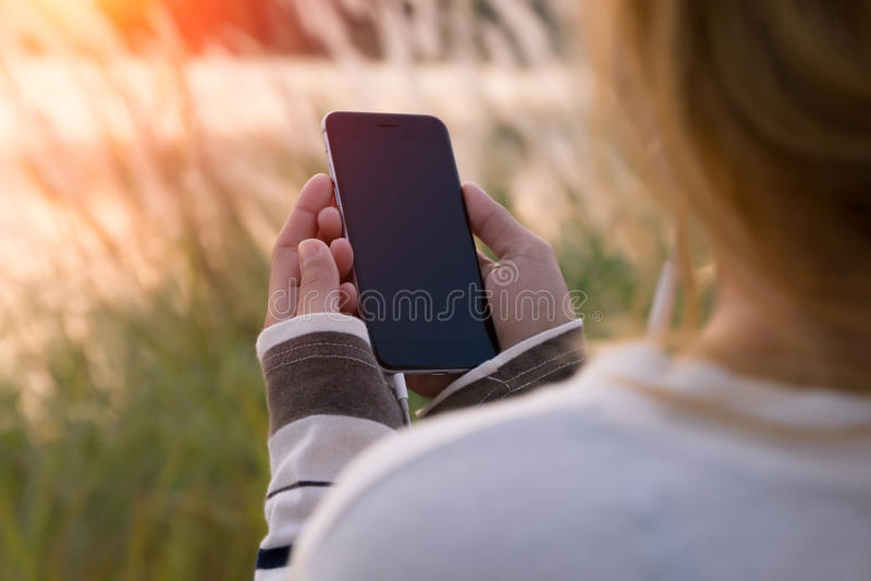 Smartphone van de vrouwenholding tijdens zonsondergang stock foto's