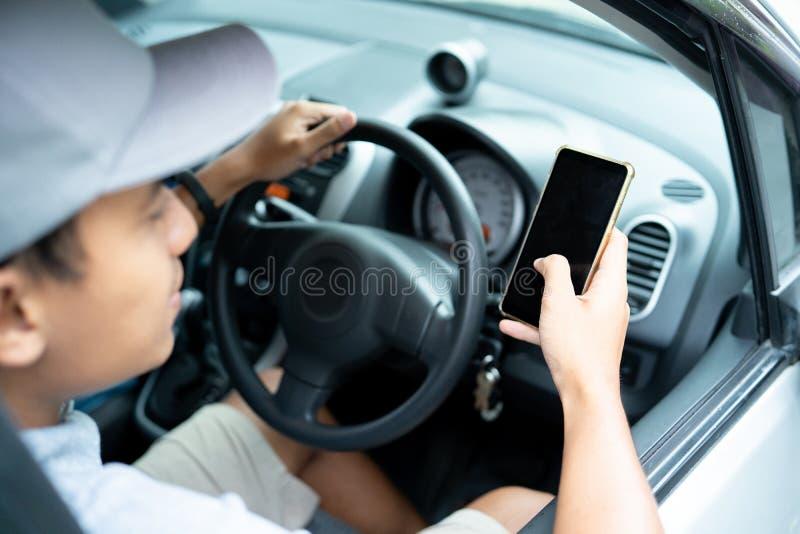 Smartphone van het bestuurdersgebruik wanneer aandrijving een auto om te navigeren royalty-vrije stock afbeeldingen