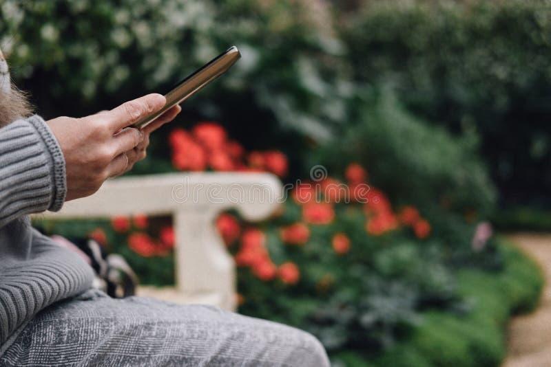 smartphone van het vrouwengebruik in tuin Meisjeszitting op bank in park P stock foto's