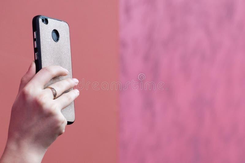 Smartphone in vrouwelijke hand met een gouden ring op een vinger Foto of video op een mobiele telefoon concept het moderne bloggi stock foto