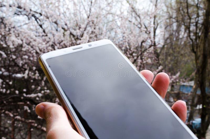 Smartphone w r?ce r?ka telefon Telefon na ulicie z lekkim odbiciem obrazy stock