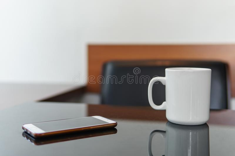 Smartphone and white cup of coffee on a table in cafe royalty free stock photography