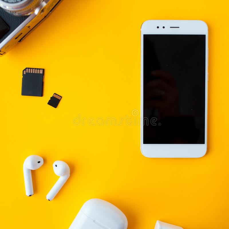 Smartphone and wireless headphones. Mobile phone and accessories stock photo