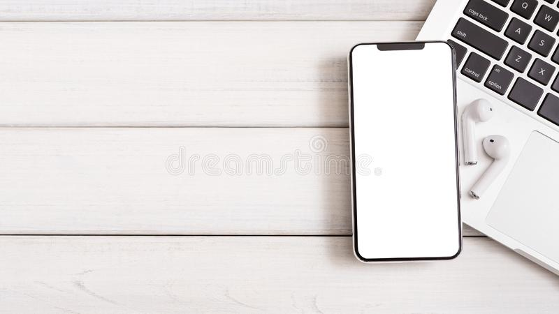 Smartphone with wireless white headphones on laptop keyboard royalty free stock photography