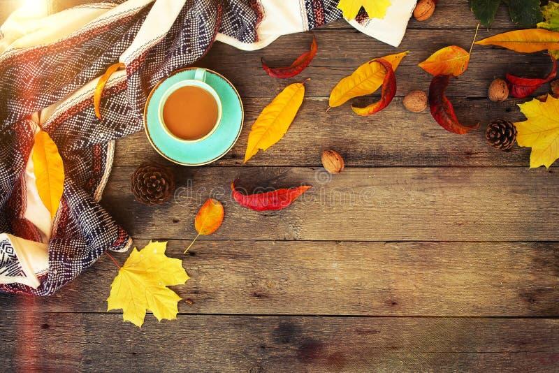 Smartphone, xícara de café e um pão picado em um fundo de madeira com folhas de outono Conceito de outono imagem de stock royalty free