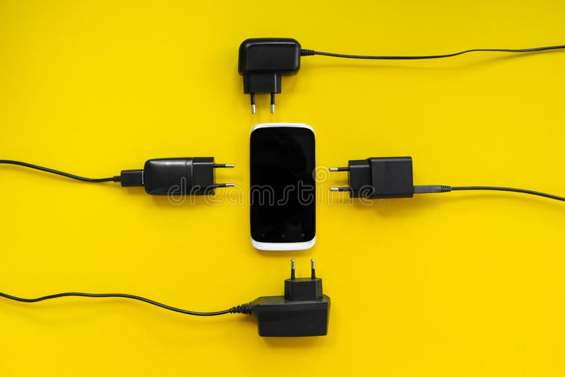 Smartphone y cargadores alrededor en un fondo amarillo, concepto imagen de archivo