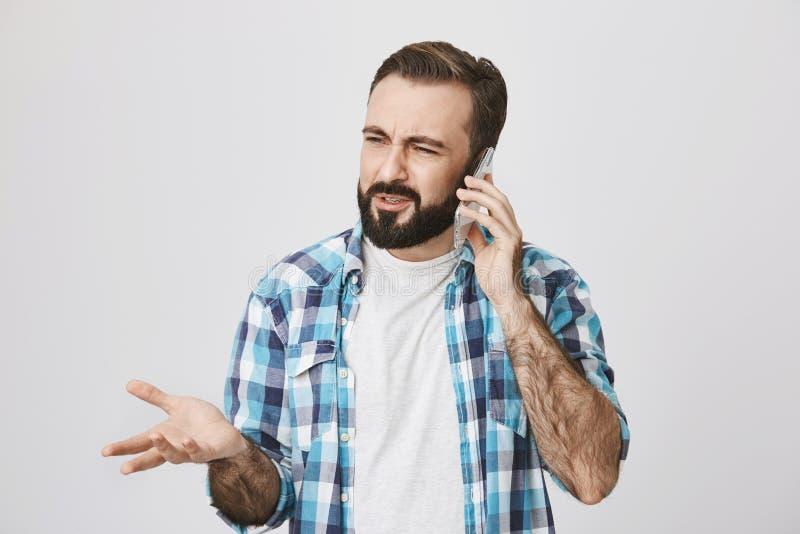 Smartphone y concepto del anuncio Varón adulto con la barba y bigote que expresa la frustración, gesticulatins mientras que fotografía de archivo libre de regalías