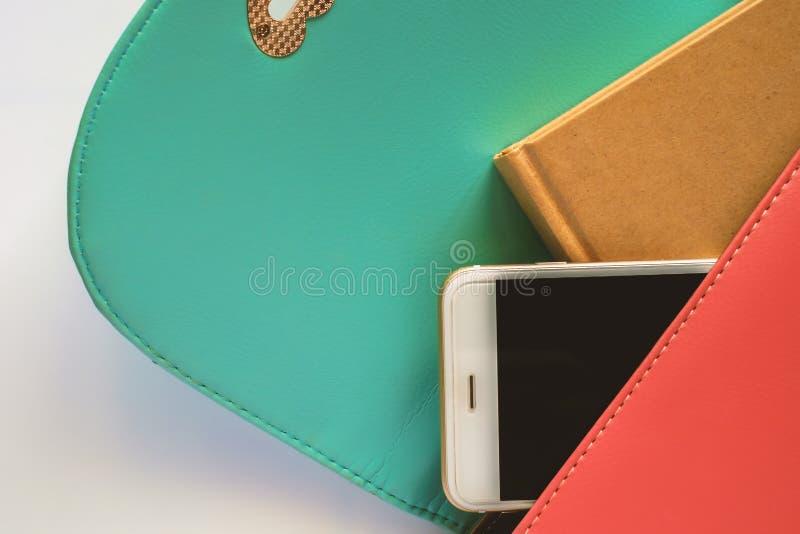 Smartphone y cuaderno en bolso fotografía de archivo libre de regalías