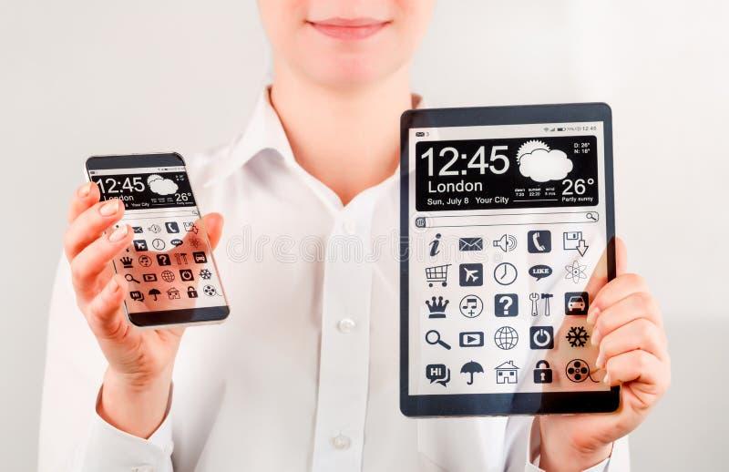 Smartphone y tableta con la pantalla transparente en manos humanas fotos de archivo