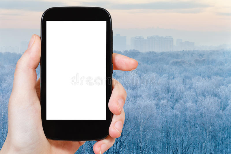 Smartphone z cięcia out parawanowym i zamarzniętym lasem zdjęcie royalty free