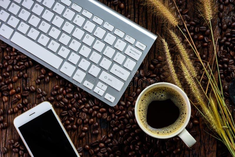 Smartphone z czarnym pustym ekranem, klawiaturą, filiżanką, suchej trawy kwiatami i piec kawowymi fasolami na drewnianym tekstury fotografia stock