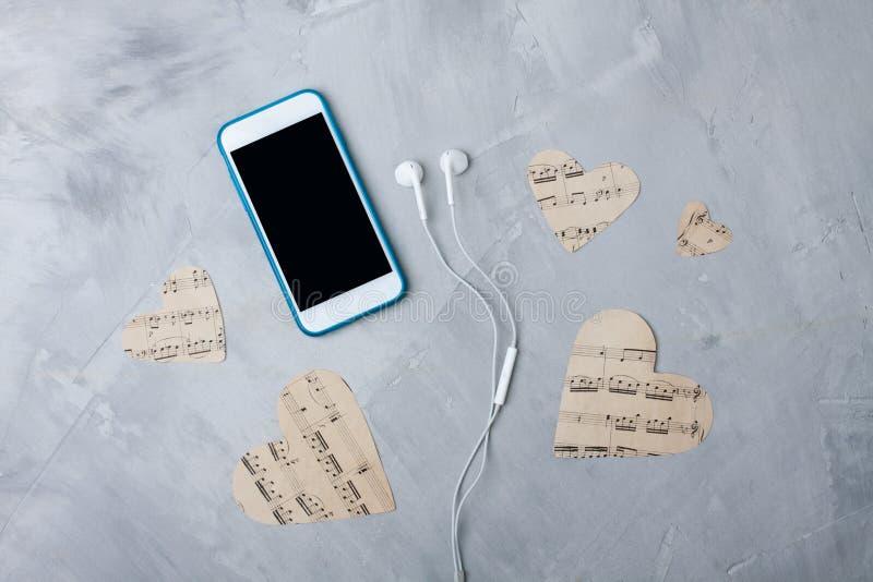 Smartphonen för Flatlay musiksammansättning eller mobiltelefonen, papper hör royaltyfri foto