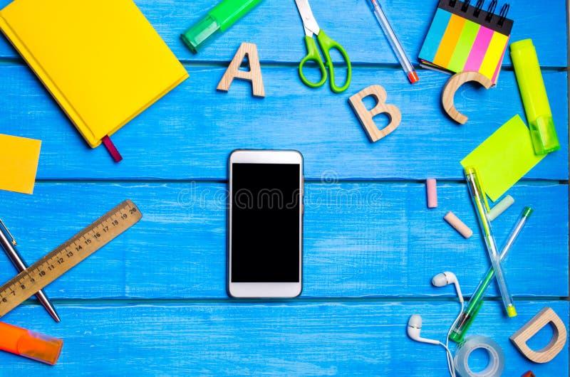 Smartphonen ligger bland skolatillförselna på den blåa trätabellen av studenten Begreppet av studien och utbildning arkivbilder