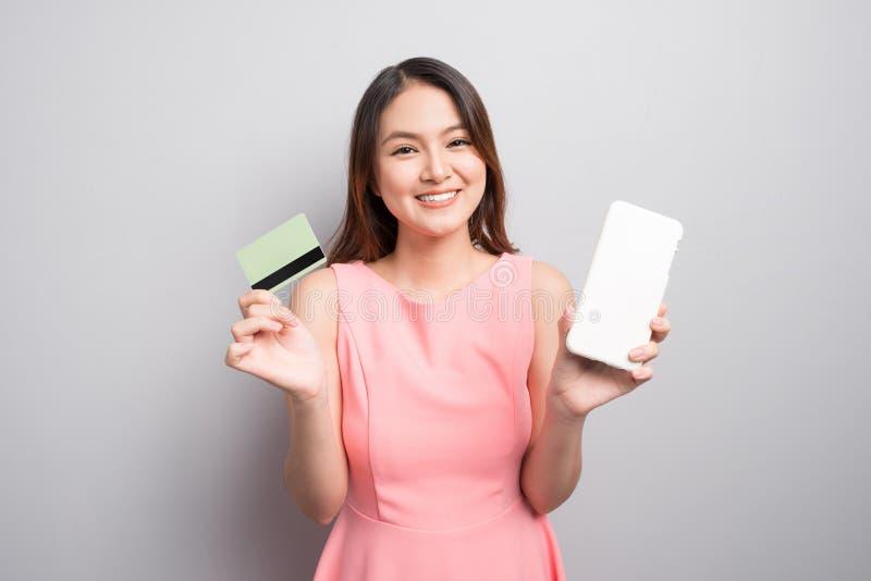 Smartphonen och showen för charmig asiatisk kvinnahand krediterar den hållande bilen royaltyfri bild