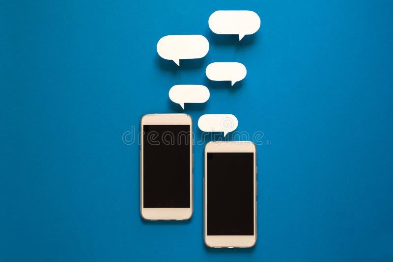 Smartphones con i fumetti di carta su fondo blu Concetto di comunicazione immagine stock