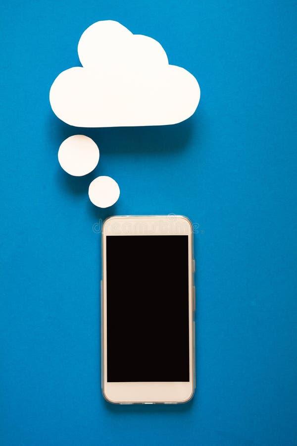 Smartphones con i fumetti di carta su fondo blu Concetto di comunicazione fotografia stock
