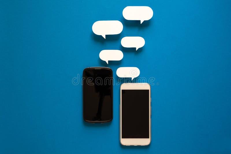 Smartphones con i fumetti di carta su fondo blu Concetto di comunicazione immagine stock libera da diritti