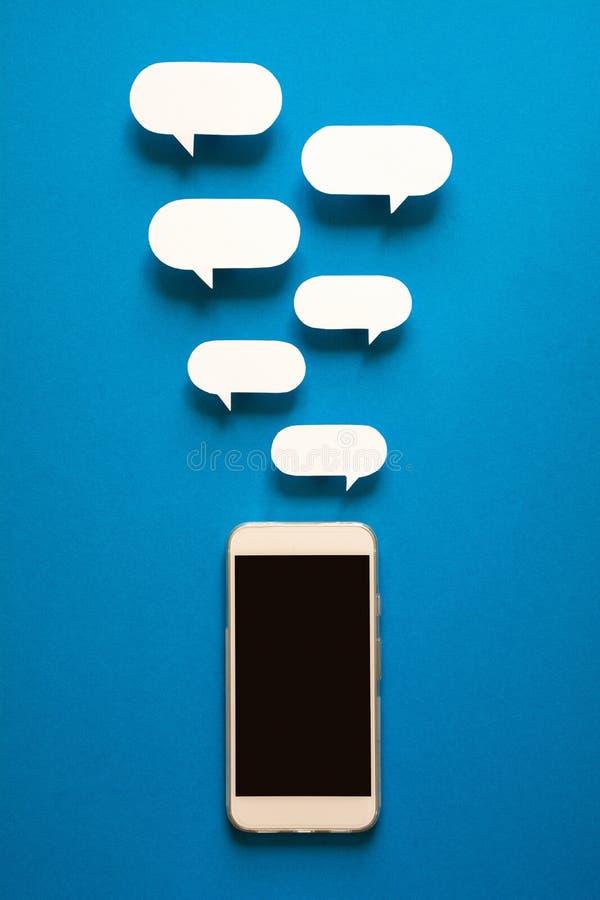 Smartphones con i fumetti di carta su fondo blu Concetto di comunicazione immagini stock