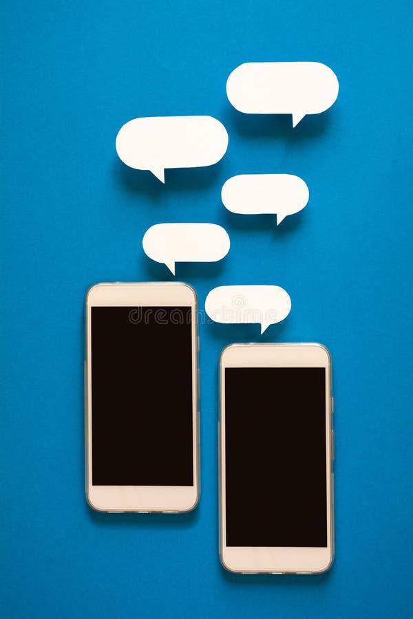 Smartphones con i fumetti di carta su fondo blu Concetto di comunicazione fotografie stock