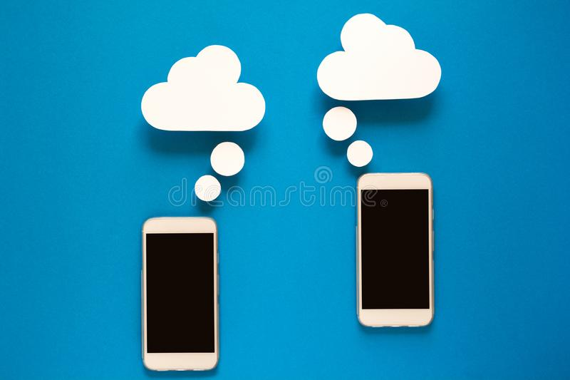 Smartphones con i fumetti di carta su fondo blu Concetto di comunicazione fotografie stock libere da diritti