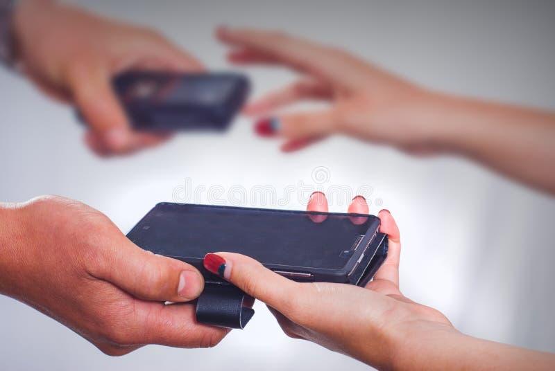Smartphones da troca do homem e da mulher imagem de stock