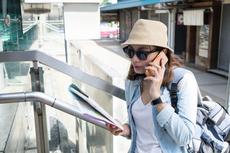 Smartphones del uso del viajero de la mujer y sostener un mapa para el viaje del hallazgo imágenes de archivo libres de regalías