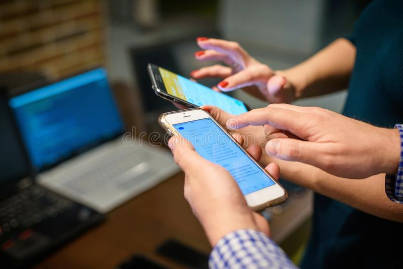 Smartphones in humans` hands, blurred laptop on a background. royalty free stock photo