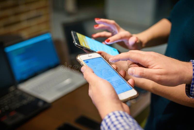 Smartphones in mani del ` degli esseri umani, computer portatile vago su un fondo fotografia stock libera da diritti
