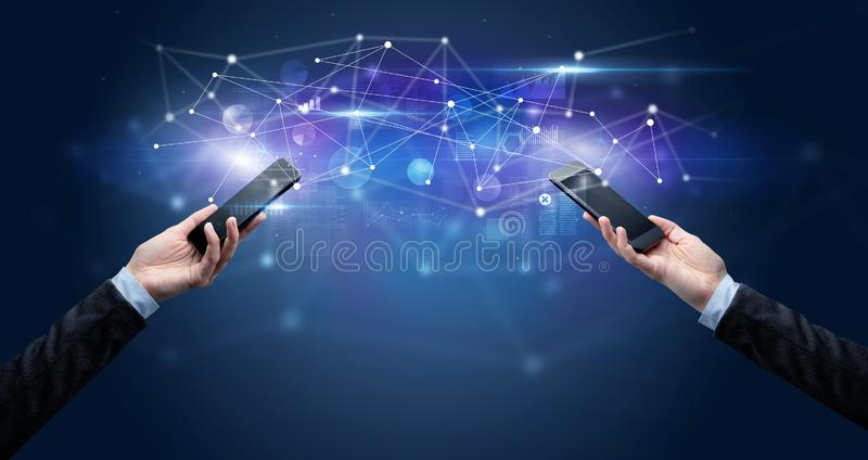 Smartphones sharing business data. Close up of two hands holding smartphones and sharing business data royalty free stock photo