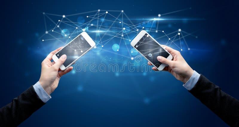Smartphones sharing business data stock photos