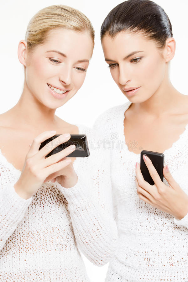 smartphones två unga kvinnor arkivfoton