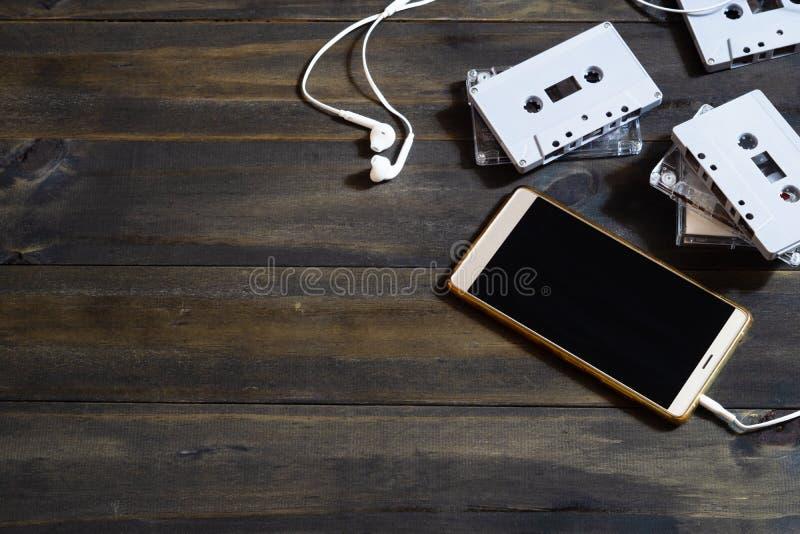 Smartphones und Kassetten auf hölzernem Hintergrund Modernes und Retro- Technologiehintergrundkonzept Draufsicht mit Kopienraum lizenzfreies stockfoto