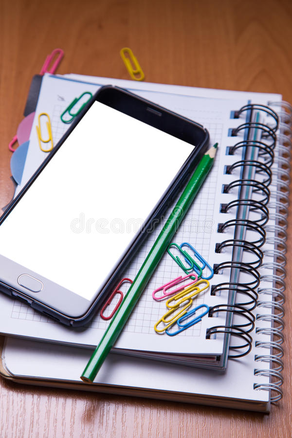 Smartphote en el cuaderno en oficina imágenes de archivo libres de regalías