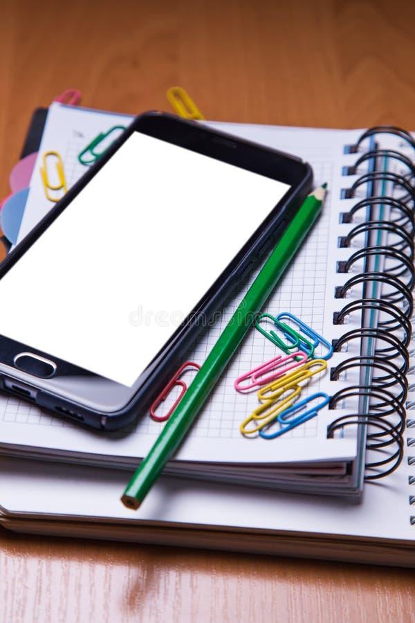 Smartphote en el cuaderno en oficina fotografía de archivo