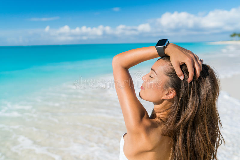 Smartwatch beach woman relaxing with wrist watch. Smartwatch woman relaxing on beach wearing smart wrist watch for activity tracker for an active lifestyle on stock image