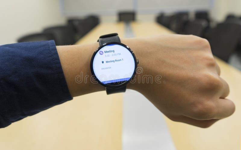 Smartwatch do olhar do homem de negócio na programação da agenda da mostra da sala de reunião quando onde e organizador fotografia de stock