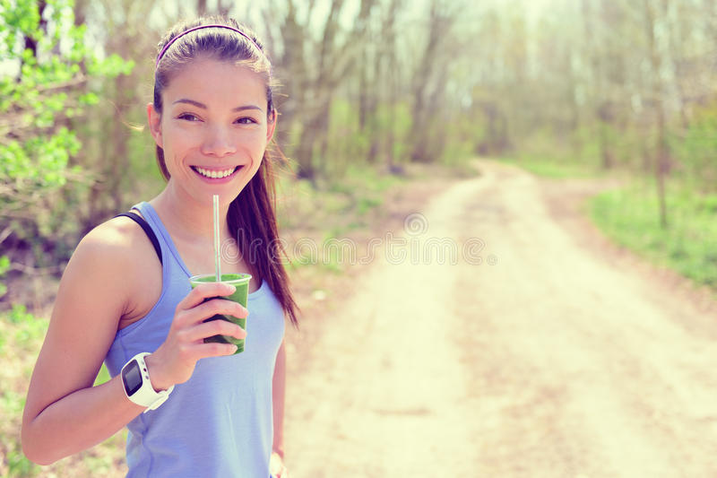Smartwatch girl drinking healthy green smoothie. Healthy fitness girl drinking green spinach vegetable smoothie wearing smartwatch heart rate monitor during stock image