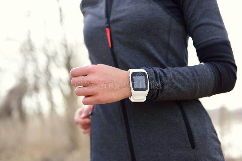 Smartwatch kvinnaspring med bildskärmen för hjärtahastighet arkivbild