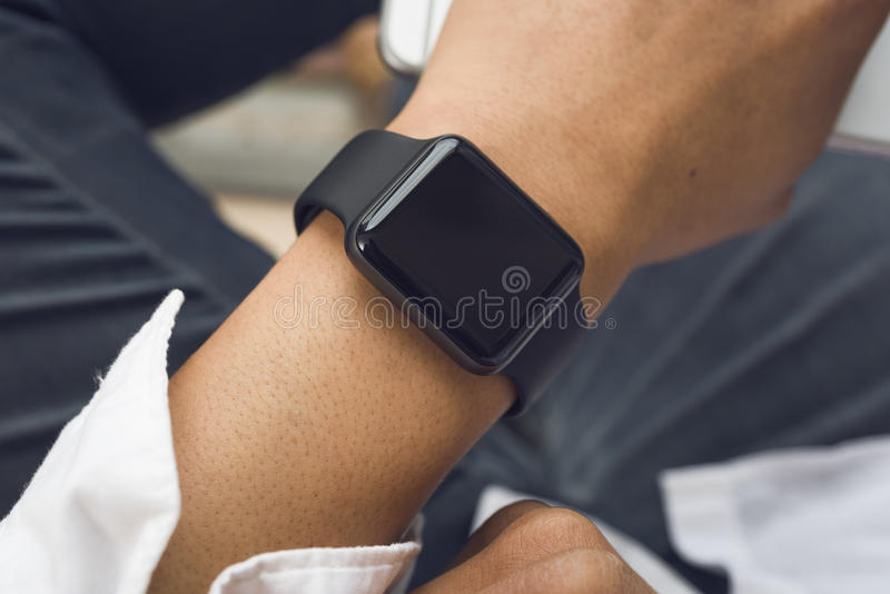 Smartwatch. On mens wrist on lap stock images