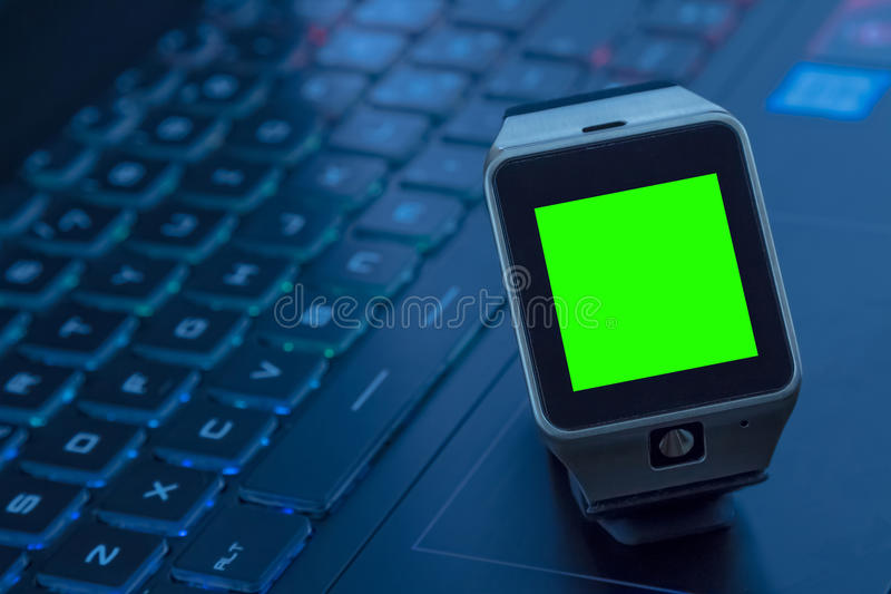 Smartwatch near computer pc keyboard with chroma key green screen. New technology concept royalty free stock images