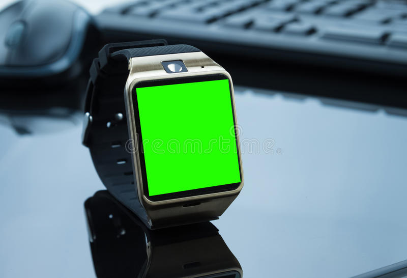 Smartwatch near computer pc keyboard and mouse with chroma key green screen. New technology concept stock photo