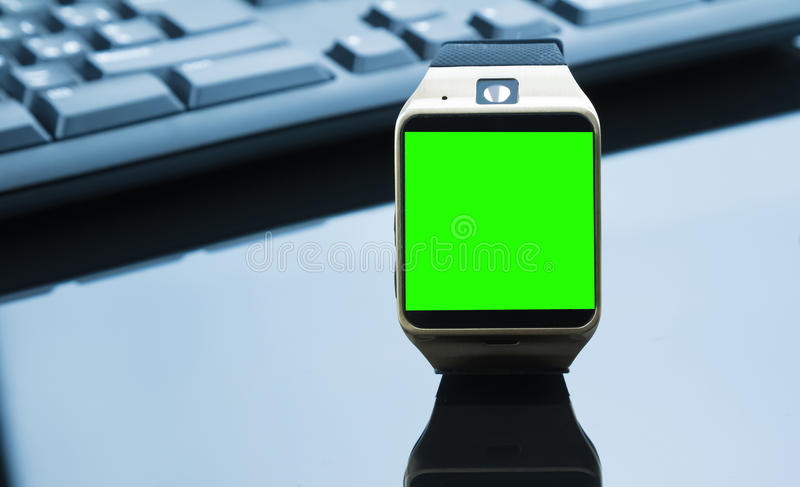 Smartwatch near computer pc keyboard and mouse with chroma key green screen. New technology concept royalty free stock images