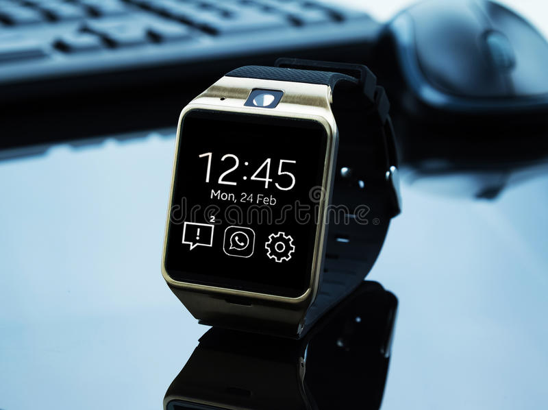 Smartwatch near computer pc keyboard and mouse. New technology concept stock photos
