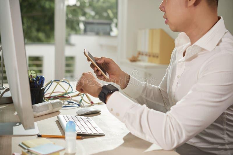 Smartwatch se reliant d'homme d'affaires avec le t?l?phone portable images stock